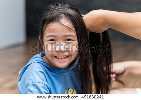 Mom hands weaving braids with her Asian daughter at home