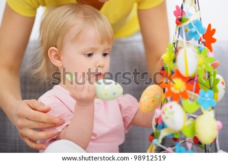 Mom helping baby made Easter decoration