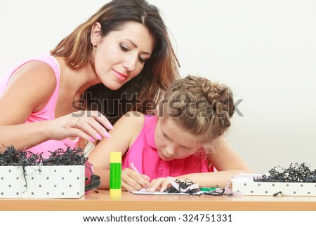 Mom helping daughter with homework. Parenting, cooperation, common fun