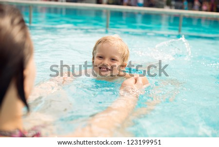 Mom helping her son to swim, both having fun - stock photo