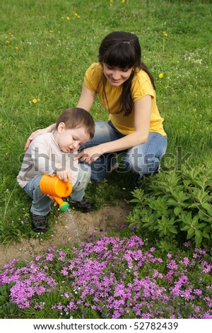 Mom helps son watered flowers with funnel