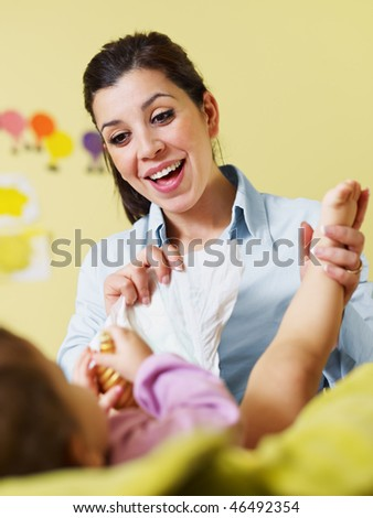 mom holding her daughter and changing diaper. Vertical shape, Copy space - stock photo