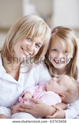 Mom holding the baby in her arms and her daughter - stock photo