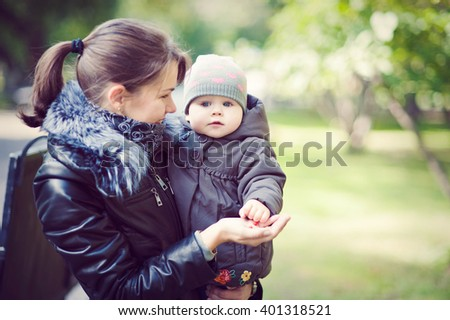 Mom holds daughter on hands while walking in the Park, cool weather.