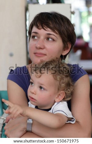 Mom hugs her toddler at the cafe - stock photo