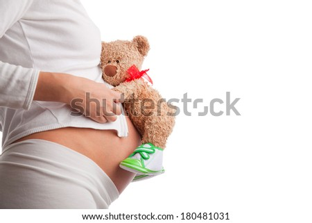Mom in pregnancy holding a teddy bear - stock photo