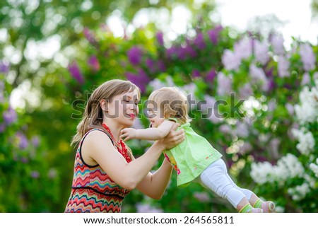 Mom in the park playing with her baby, tossing it up. Happy baby laughing. blooming lilac - stock photo