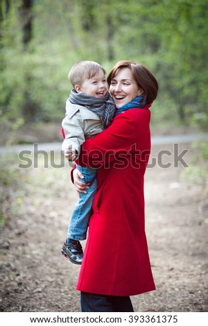 Mom in the red coat is holding his son, they laugh and play, forest background, vertical.