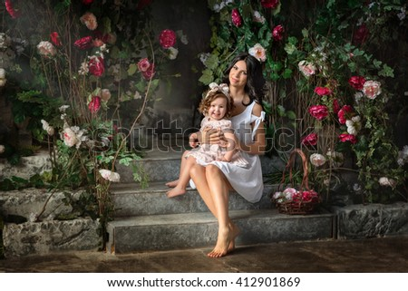 Mom in white sundress holding in her arms little girl sitting in the garden of rose bushes - stock photo