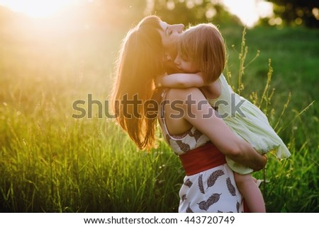 Mom kisses and hugs daughter on nature in sunset light, family, motherhood, child - stock photo