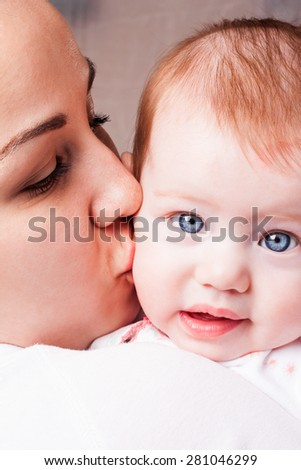 Mom kisses the cheek of her child
