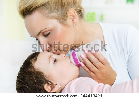 Mom kissing her baby little girl while she drinking milk from bottle.Baby feeding.Shallow doff
