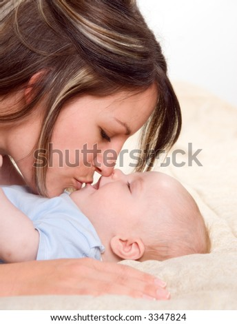 mom kissing her lovely baby boy portrait