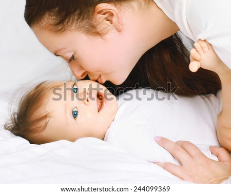 Mom kissing little baby on the bed at home