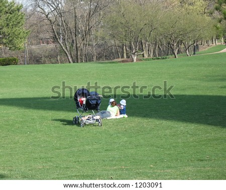 mom lying with twins on grass on a hill