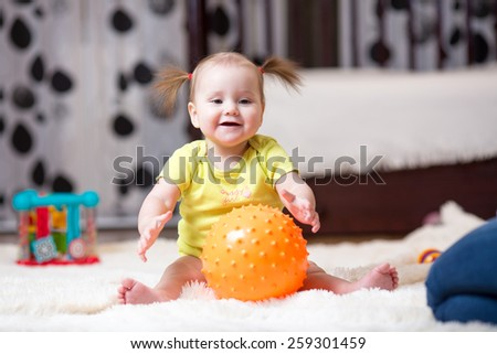 mom playing ball with little child at home - stock photo