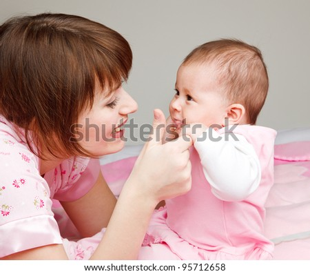 Mom playing with baby - stock photo