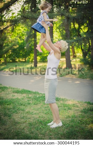 Mom playing with daughter in the park. Concept of a happy family