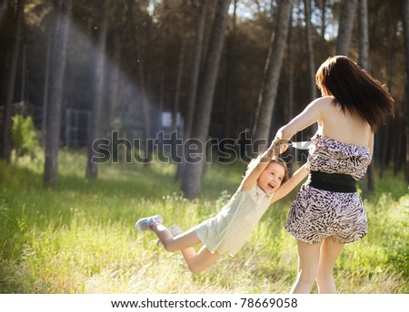Mom playing with her daughter in sunny outdoors - stock photo