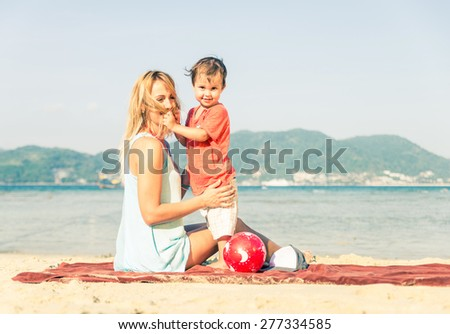Mom playing with her handsome son on the beach - Happy family on vacation on a tropical beach - stock photo