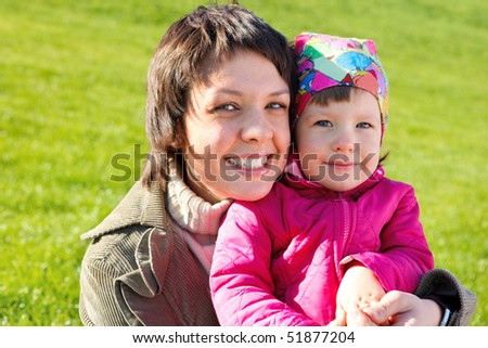 Mom playing with her toddler daughter in the outdoor - stock photo