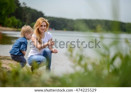 Mom plays with her son by the river