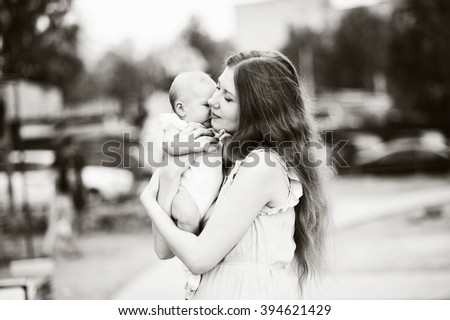 Mom presses tight to me baby, black and white image, horizontal. - stock photo