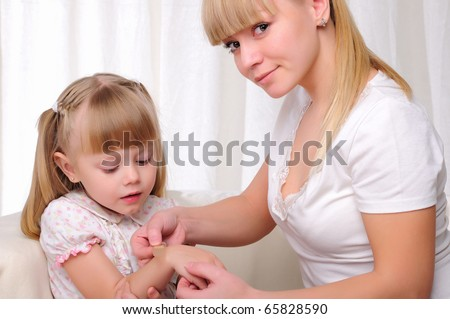 Mom puts her baby daughter plaster on the sore arm - stock photo