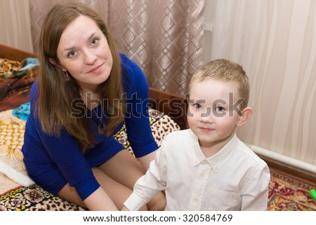 Mom puts her son in fancy clothes ready for the holiday - stock photo