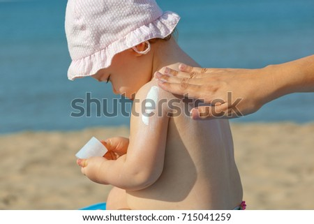 Mom puts sunscreen on the shoulders of her one year old daughter.