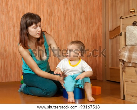 Mom puts the baby on the potty at home - stock photo