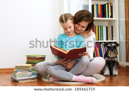 Mom reading a book her little daughter. beside them sitting dog - stock photo