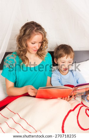 Mom reading a book to her son laying in bed - stock photo