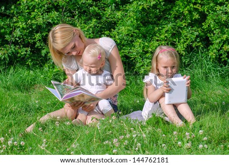 Mom reading book to daughter. Other is playing with computer. - stock photo