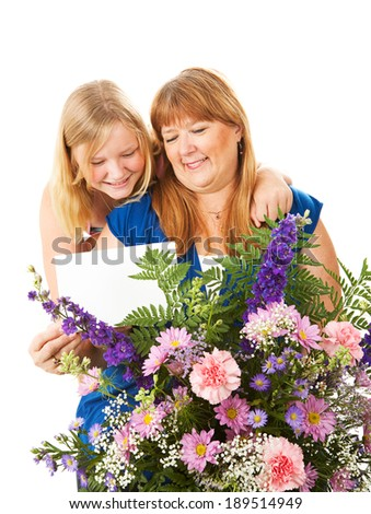 Mom receives flowers and a card from her daughter on Mother's Day.  Could also work as a birthday concept.   - stock photo