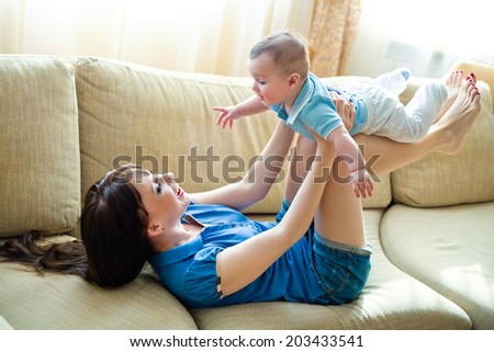 Mom rolls baby on your lap while lying on the couch - stock photo