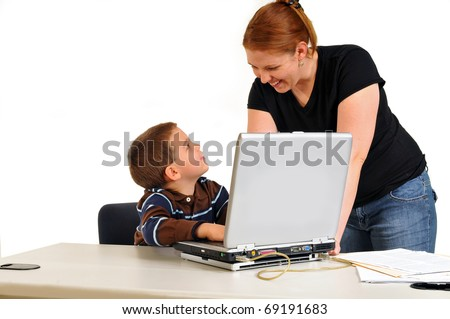 Mom smiling at son sitting at a desk with boy at laptop doing good work.
