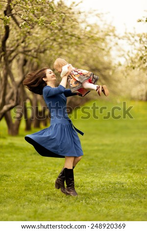 Mom spinning with adorable toddle daughter.  Long wavy black hair. Summer sunny day - stock photo