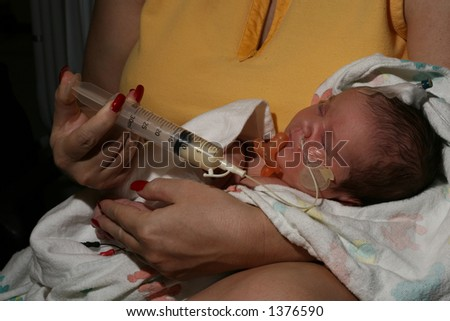 mom syringe-feeding a newborn in ICU - stock photo