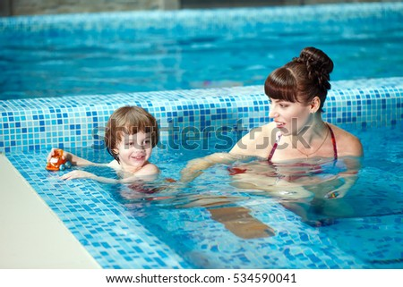 Mom teaches a child to swim in the pool.