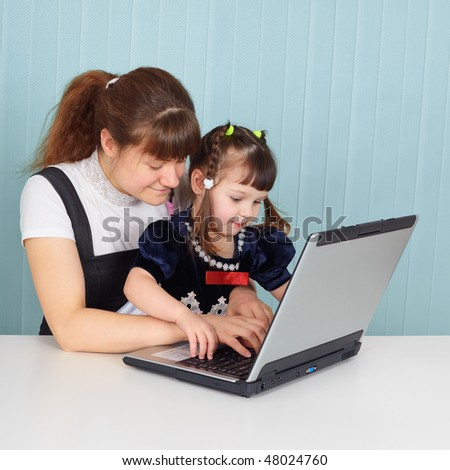 Mom teaches daughter to use a computer