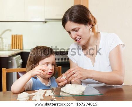 Mom teaches malekuyu girl sculpt dough figurines in the room - stock photo
