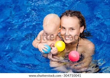 Mom teaches the child to swim  in the swimming pool - stock photo