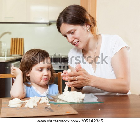 Mom teaches the girl to mold dough figurines in the room - stock photo