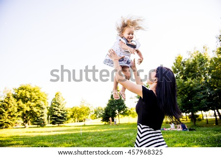 mom throws up and kisses her daughter in the Park