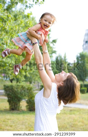 Mom throws up her year-old daughter - stock photo