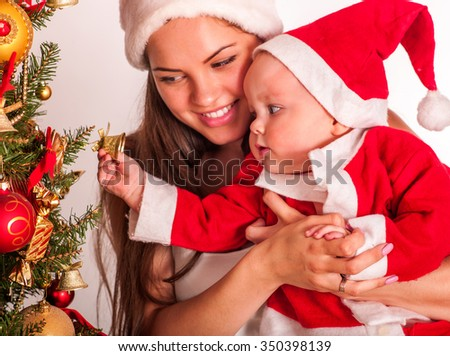 Mom wearing Santa hat holding  baby with gift box  and touch Christmas tree. - stock photo