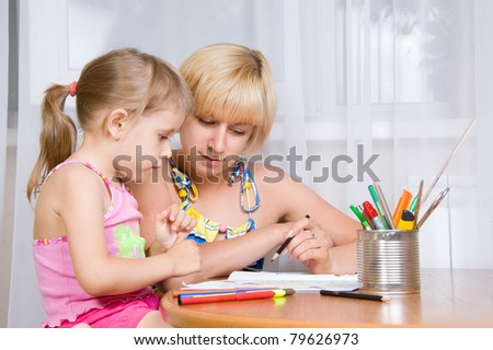 mom with a child draws with pencils