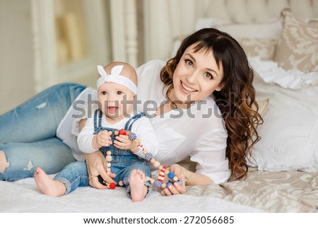 Mom with a young daughter, laughing and hugging - stock photo