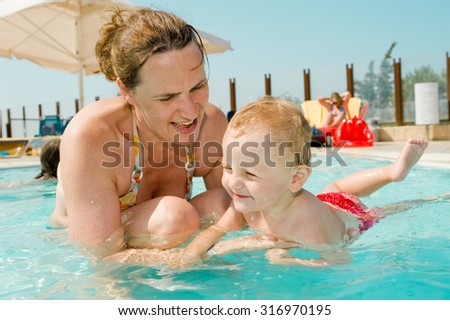 Mom with baby have a fun in the swimming pool